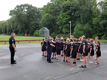 Kids being instructed how to stand in formation
