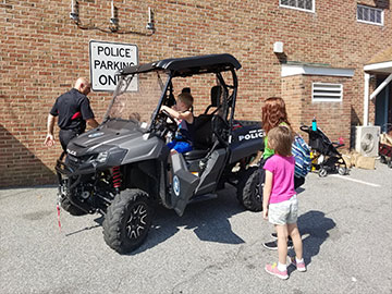 Kids sitting in the police all-terrain vehicle